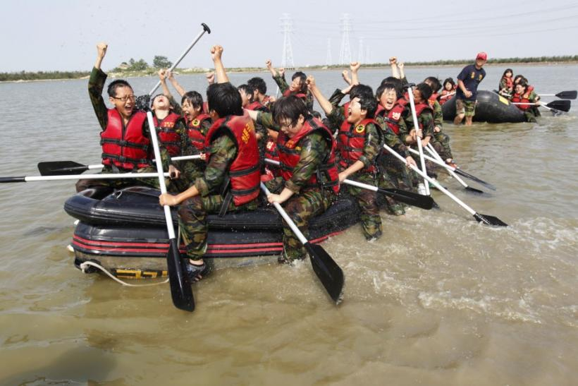 Elementary school students celebrate in a rubber boat as they participate in a summer military camp at the Cheongryong Self-denial Training Camp in Ansan