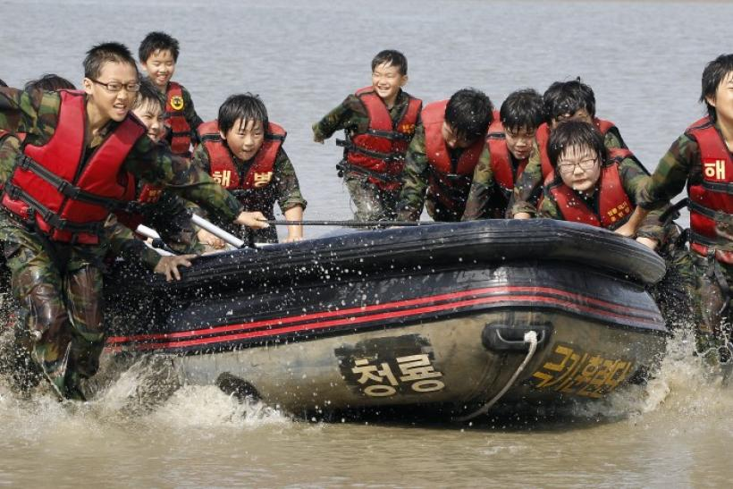 Elementary school students carry a rubber boat as they participate in a summer military camp for civilians at the Cheongryong Self-denial Training Camp run by retired marines in Ansan