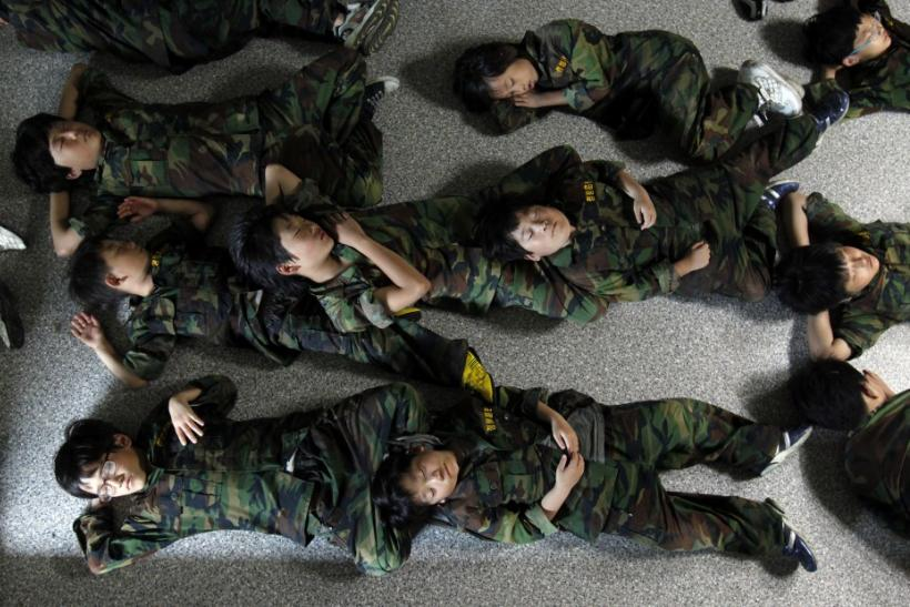 Elementary school students take a nap on a floor after a morning exercise as they participate in a summer military camp for civilians at the Cheongryong Self-denial Training Camp run by retired marines in Ansan