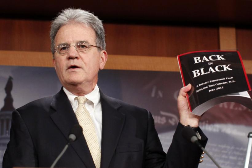 U.S. Senator Tom Coburn (R-OK) holds up a copy of his deficit-reduction plan during a media availability in the Capitol in Washington