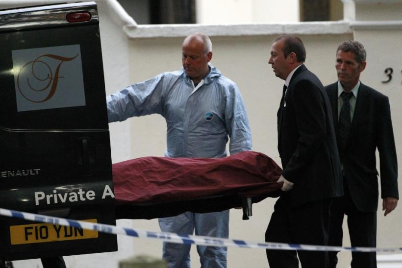 Funeral workers and a police officer bring the body of Amy Winehouse to a van outside her house in London