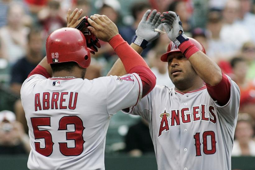 Vernon Wells of the Angels is greeted by teammate Bobby Abreu after hitting a home run against the Orioles in Baltimore