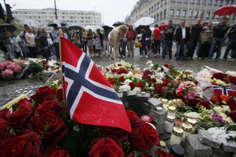 A Norwegian flag sticks out of a bunch of red roses on the market square outside the Oslo cathedral as hundreds mourn the victims of a bomb blast and a rampage