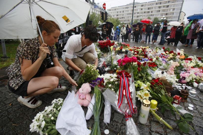 People place flowers on the cobble stones of the market square outside the Oslo cathedral to mourn the victims of a bomb blast in the capital and a rampage on an island in the countryside