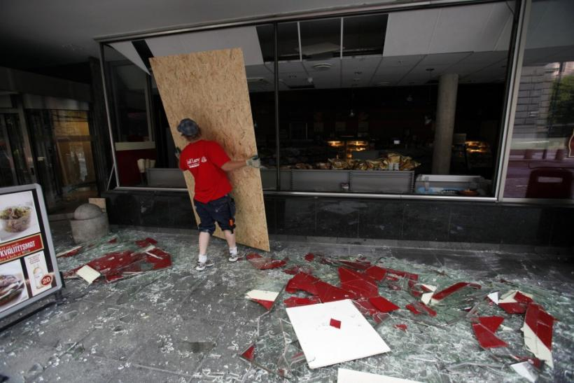 A man replaces the broken windows of a Deli shop near the blast site in the capital Oslo