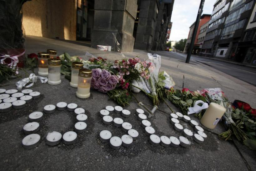 Candles and flowers are arranged on the ground near the blast site to mourn the victims of a rampage on an island and in the capital Oslo