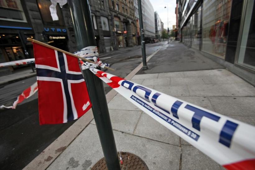 A Norwegian flag is planted on a police barrier blocking the access to the blast site in the capital Oslo