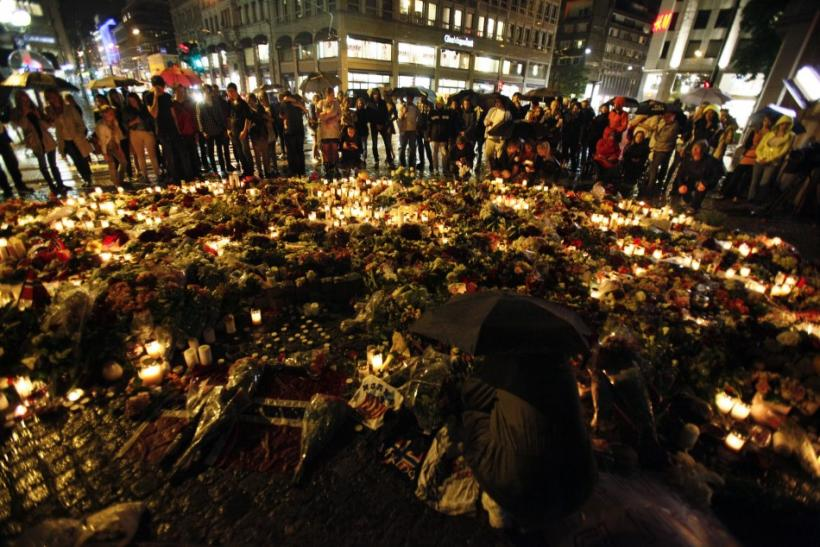 eople stand under umbrellas during heavy rain as they mourn for the for the victims of a bomb blast in the capital and a rampage on nearby Utoeya island, in front of a sea of candles and flowers, in Oslo