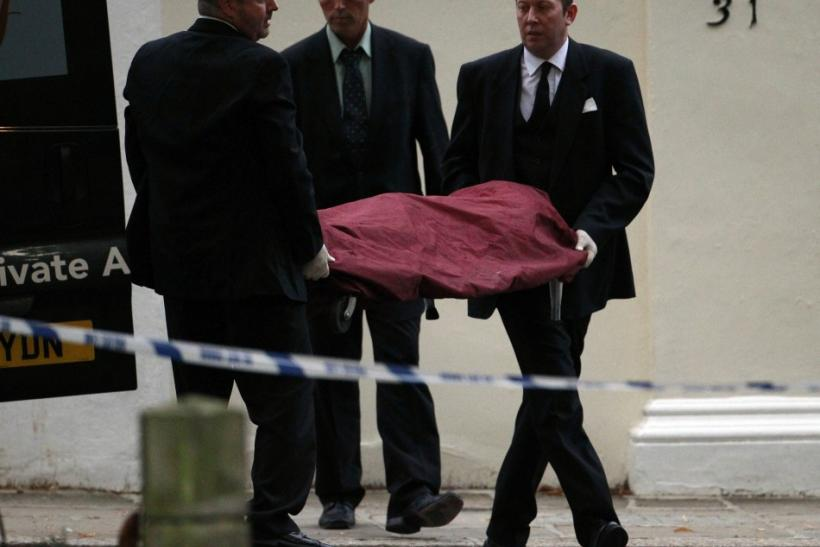 Funeral workers carry the body of Amy Winehouse outside her house in London