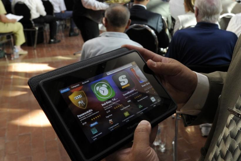 A man holds a BlackBerry PlayBook during the RIM annual general meeting of shareholders in Waterloo 12/07/2011