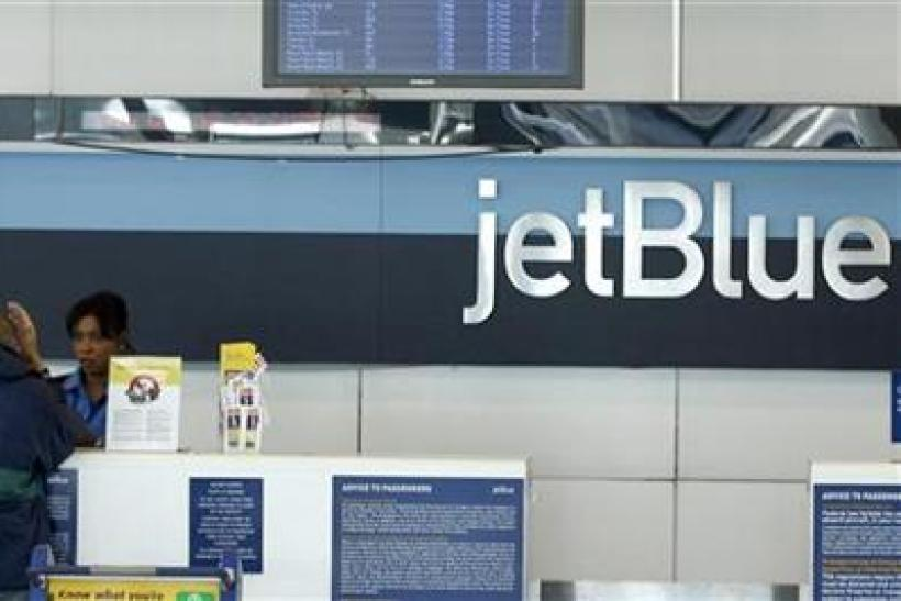 A JetBlue employee assists a customer at the check-in counter at JFK International Airport in New York