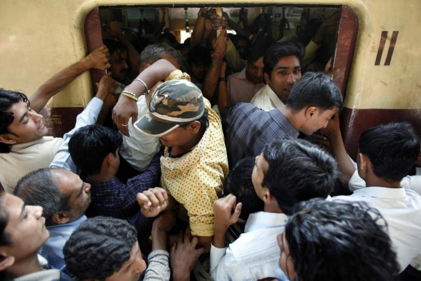 Commuters make their way into a crowded compartment of a local train in Mumbai