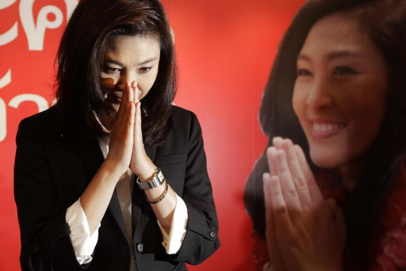 Yingluck Shinawatra greets reporters and supporters gathered at her party's headquarters after voting in general elections ended in Bangkok