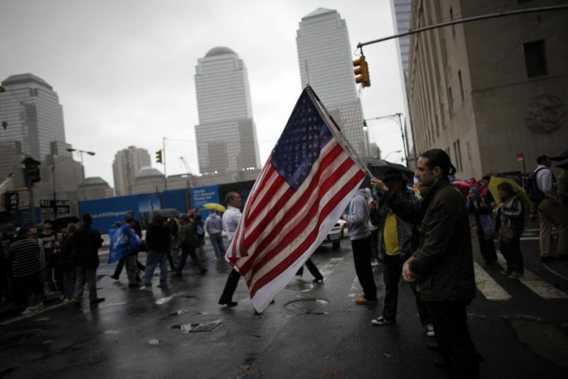 A man holds a U.S. flag while others pause for a moment of silence to pay their respects at the site of the former Twin Towers in New York