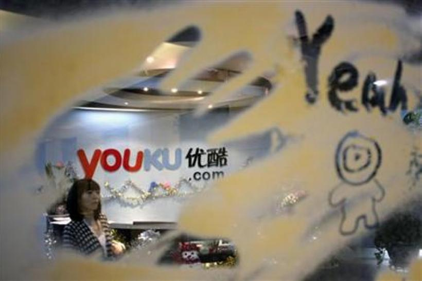 An employee is seen through a glass wall as she walks past the logo of Youku.com above the reception desk at the company's headquarters in Beijing