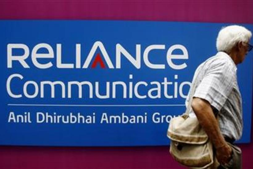 A man walks past a logo of Reliance Communication before Annual General Meeting in Mumbai