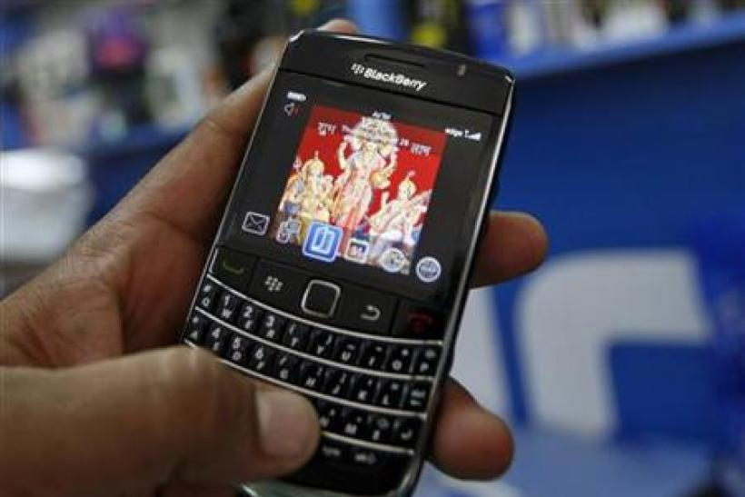 A customer holds a BlackBerry handset at a mobile phone shop in Ahmedabad
