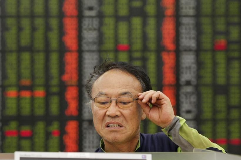 An investor reacts as he looks at a computer monitor showing stock prices in a customer lounge of a stock trading firm in Seoul