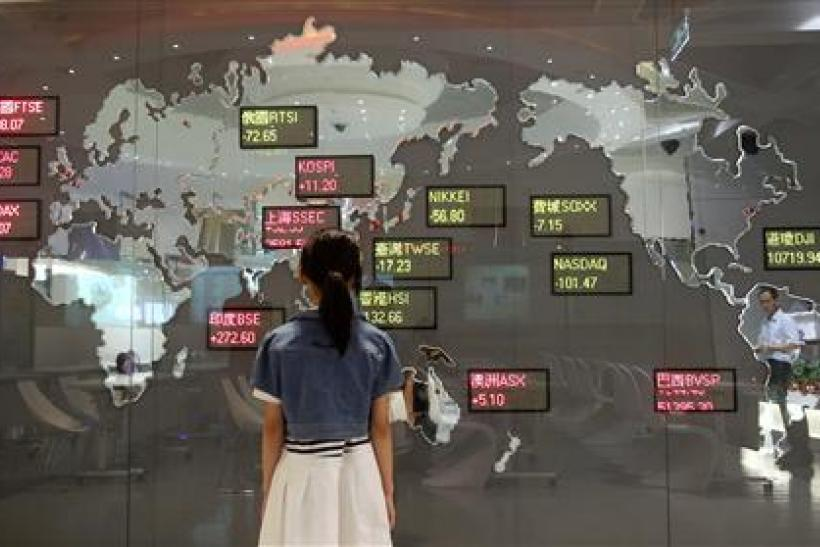 A girl looks at a board showing global stock indices at the Taiwan Stock Exchange in Taipei