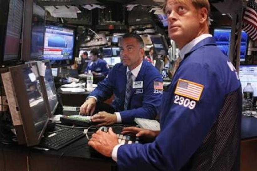 Traders look up at the days gain as they work on the floor of the New York Stock Exchange