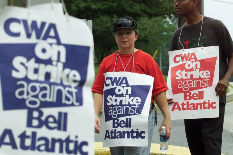 Communication Workers of America union members Lynn Oldenburg (L) and Geoffrey Lawson (R) walk the picket line at a Verizon office complex in Silver Spring, Maryland, August 7, 2000