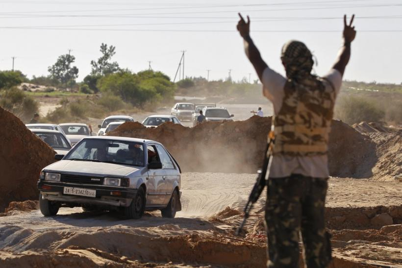 A Libyan rebel fighter raises his arms as a convoy of residents flee fighting near the coastal town of Zawiyah