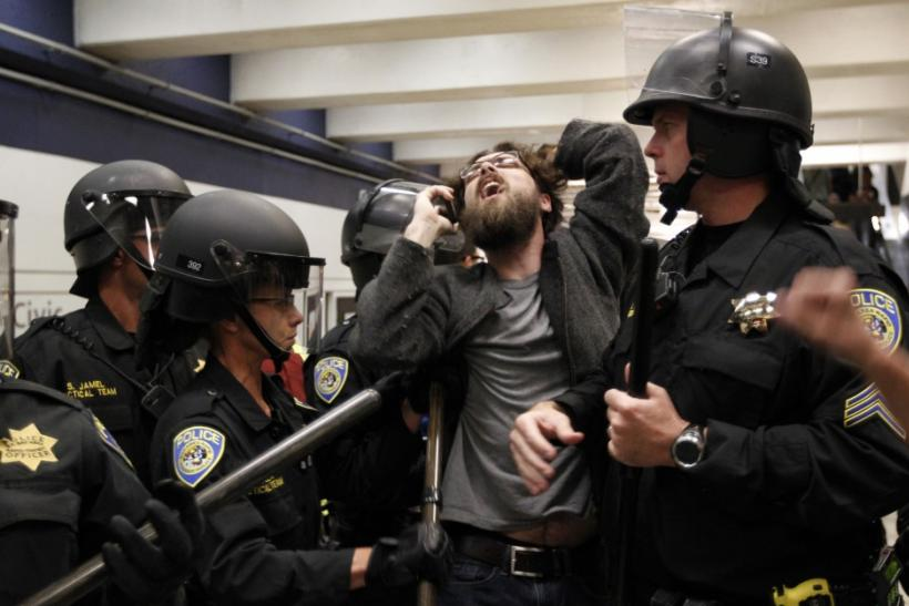 A protester is surrounded by police during a demonstration at the BART Civic Center Station in San Francisco