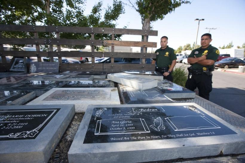 Handout photo shows San Bernardino County Sheriffs deputies looking at headstones recovered during a search of a home in Loma Linda, California