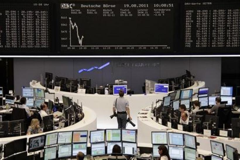 A photographer looks at the DAX index board at Frankfurt's stock exchange