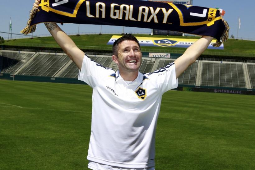 Ireland's Robbie Keane holds up a scarf after signing with MLS soccer team Los Angeles Galaxy in Carson, California