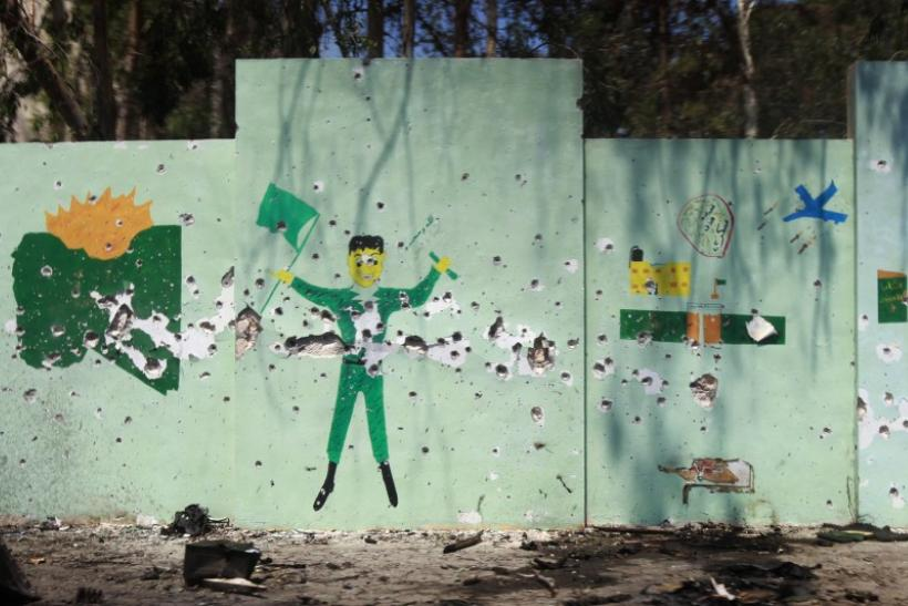 A wall mural depicting Gaddafi government propaganda is pocked with bullet holes after Libyan rebel fighters pushed pro-Gaddafi soldiers out of the center of the strategic coastal city of Zawiyah