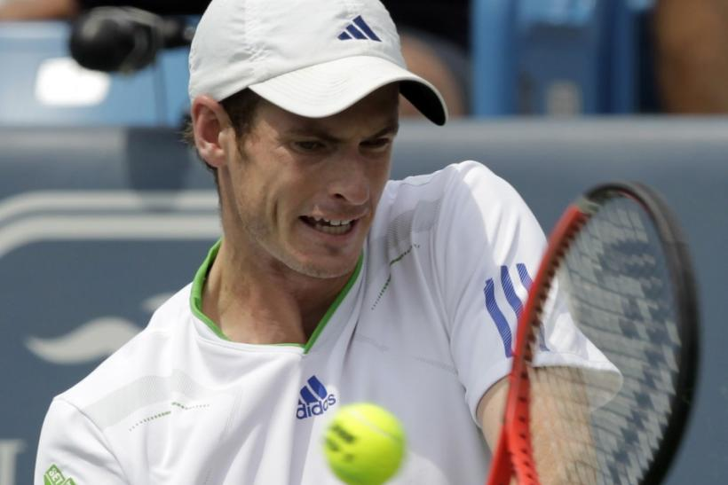 Andy Murray of Britain, hits a return to Mardy Fish of the United States, during their semifinal round match of the 2011 Cincinnati Open tennis tournament in Cincinnati