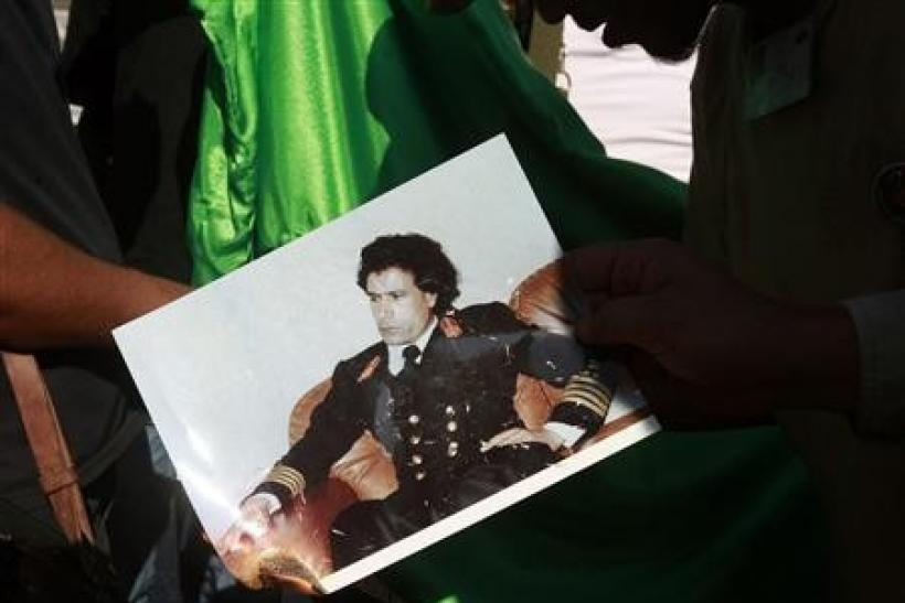 Libyan rebel fighters burn a picture of Muammar Gaddafi at a checkpoint in Tripoli's Qarqarsh district