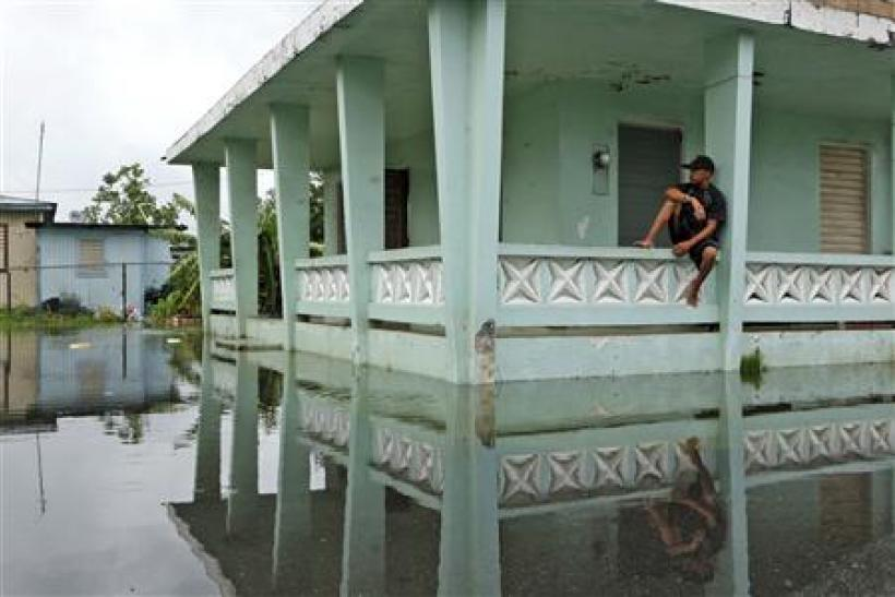 A man sits outside his home after Hurricane Irene hit the municipality of Loiza