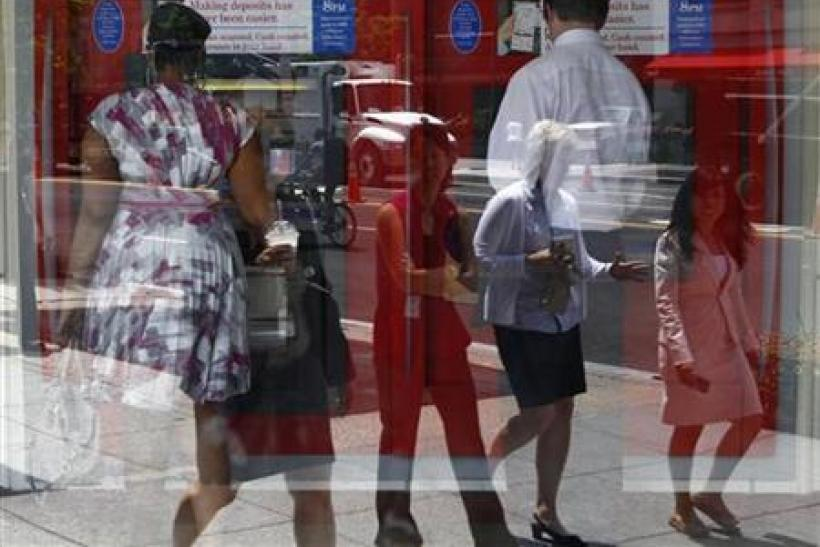 Pedestrians are reflected in the window as customers conduct transactions at a Bank of America ATM in Washington
