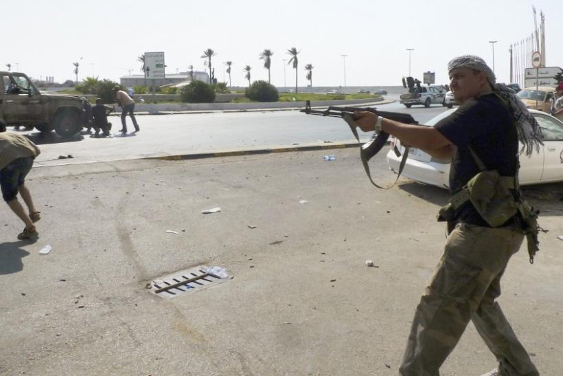 Libyan rebel fighters return fire during an attack by pro-Gaddafi forces after rebels seized a Gaddafi army women's officer training center in Tripoli