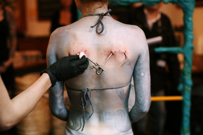 Blood is wiped from the back of British performance artist Alice Newstead after she was suspended from shark hooks at a cosmetic shop in San Francisco