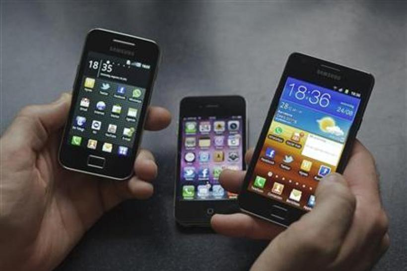 A man holds a Samsung S II and Samsung Ace smartphones next to an Apple iPhone 4 in Houten