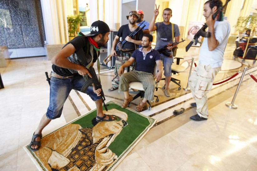A rebel steps on a poster of Libya's leader Muammar Gaddafi at Rixos hotel in Tripoli