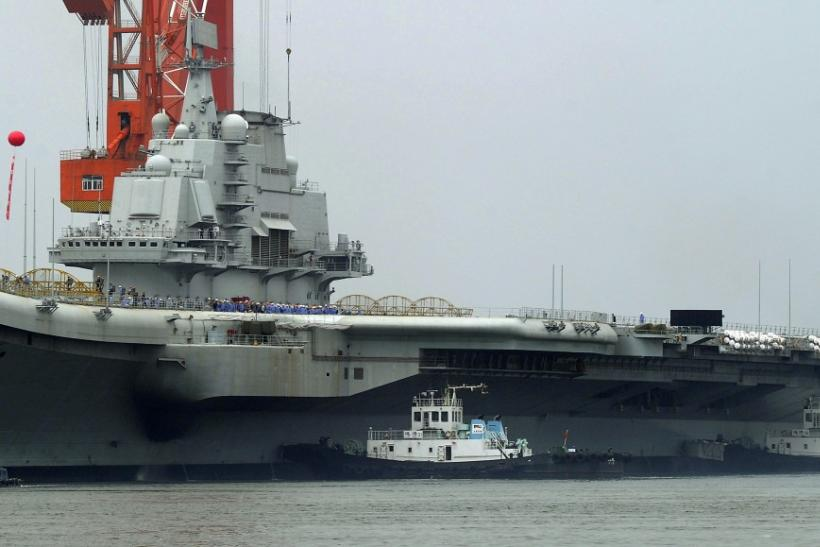 Workers are seen on the deck of China's first aircraft carrier, which finished its maiden sea trial and arrived at Dalian Port, Liaoning province