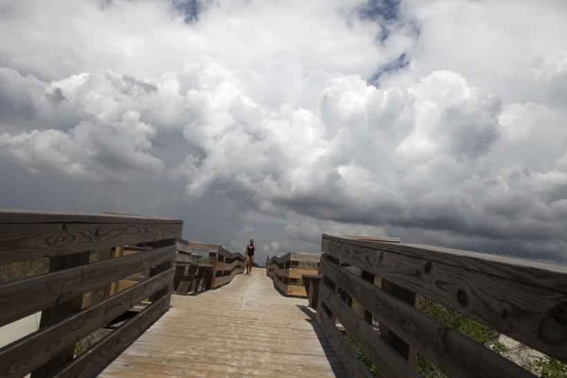 Storm clouds loom as a beachcomber walks on a beach access ramp on the west end of Sunset Beach, North Carolina