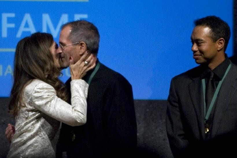 Maria Shriver (L) kisses Steve Jobs (C), chief executive officer of Apple Inc., as golfer Tiger Woods watches after Jobs and Woods were inducted into the California Hall of Fame in Sacramento, California