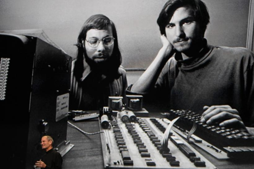 "Apple Chief Executive Officer Steve Jobs stands beneath a photograph of him and Apple-co founder Steve Wozniak from the early days of Apple during the launch of Apple's new ""iPad"" tablet computing device in San Francisco, California"
