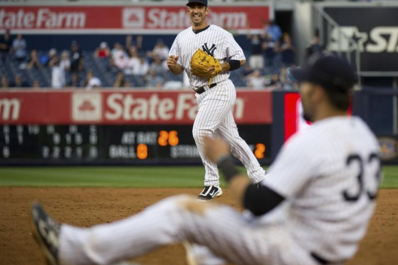 Yankees' Posada grins as he threw out Athletics' Recker for the final out in New York