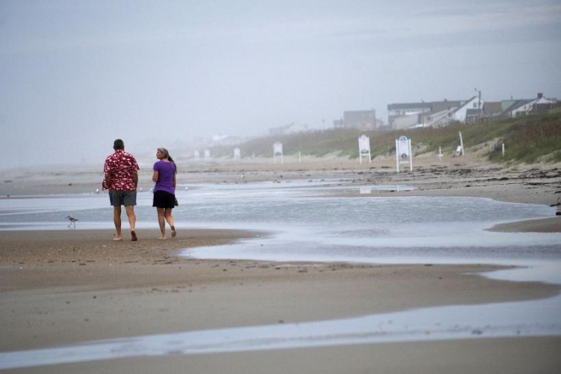 Visitors walk along the beach at high tide the day before the expected landfall of Hurricane Irene in Atlantic Beach