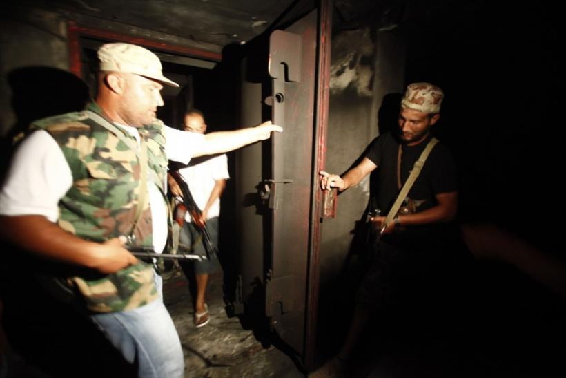 Rebel fighters check an armoured door at a tunnel in the ransacked Bab al-Aziziya compound of ousted Libyan leader Muammar Gaddafi in Tripoli