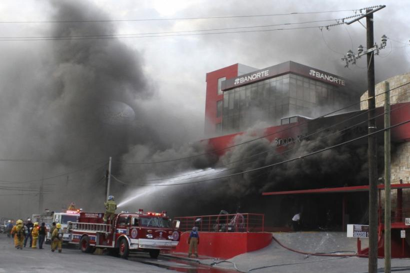 Smoke billows out of a building housing a casino as firefighters try to extinguish the fire after an attack in Monterrey