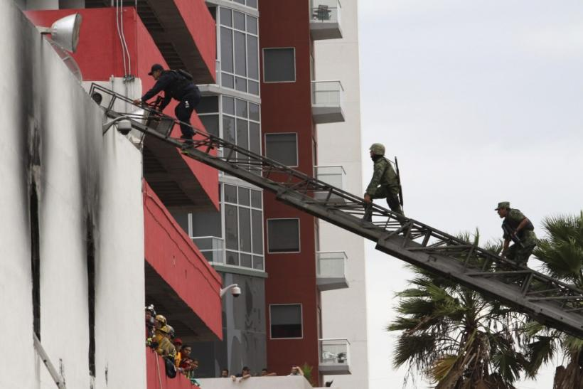 Police and soldiers climb up a ladder to enter a building housing a casino after an attack in Monterrey