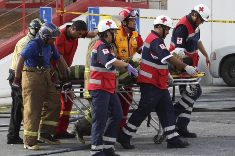 Firefighters transport an injured colleague on a stretcher after an attack on a casino in Monterrey