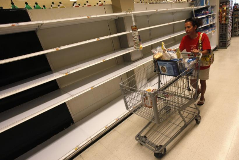 A shopper passes empty shelves while looking for bottled water at a supermarket in Long Beach on Long Island, New York